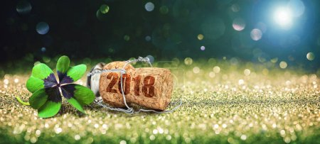 Greeting card with four leaf clover and champagne cork