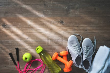 Fitness equipment, healthy food, sneakers, water bottle and towe