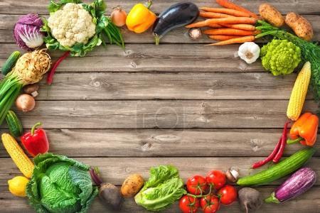 Photo pour Cadre de légumes frais assortis sur fond bois - image libre de droit