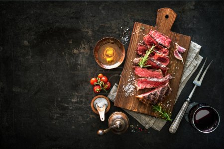 Photo for Sliced medium rare grilled beef ribeye steak on cutting board on dark background - Royalty Free Image