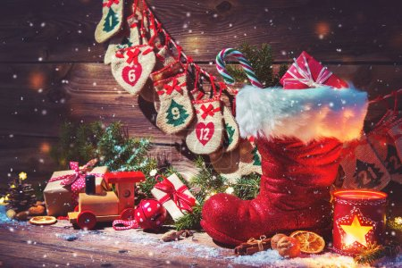 Advent calendar and Santa's shoe with gifts on rustic wooden bac