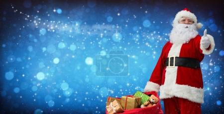 Photo for Santa Claus with a bag full of presents shows thumbs up - Royalty Free Image