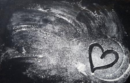 Photo pour Fond de cuisson avec forme de coeur et farine sur la table noire. Espace de copie pour le texte. Vue du dessus - image libre de droit