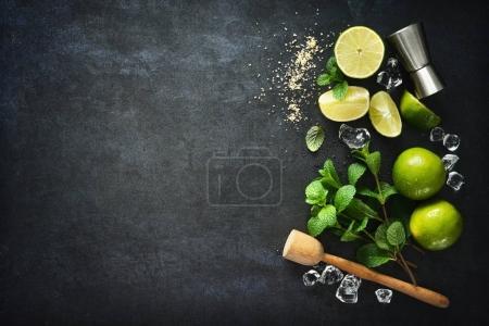 Photo pour Fabrication de cocktail Mojito. Menthe, citron vert, glace ingrédients et ustensiles de bar - image libre de droit