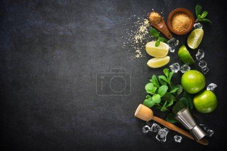 Photo pour Un cocktail mojito. Menthe, lime, ingrédients glacés et ustensiles de bar - image libre de droit