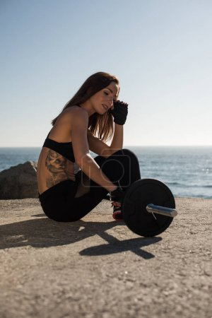 Photo for Fitness woman with tattoos lifting weights - Outdoor - Royalty Free Image