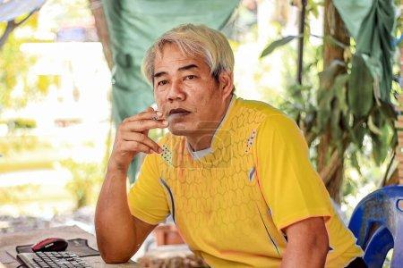 Mann raucht feierlich eine Zigarette und starrt mit Rauch vor sich hin