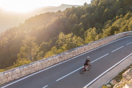 Photo for Young female cyclist riding on sunset ray glissened road high in spainish mountains - Royalty Free Image