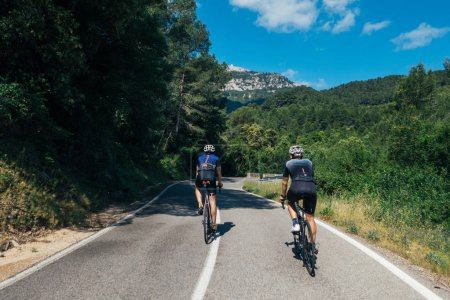 Photo for Two male cyclists dressed in navy blue clothing racing, climbing narrow road - Royalty Free Image