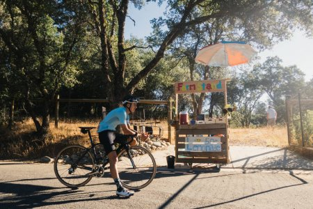 Photo for Fit male cyclist in blue jersey, kit standing over black bicycle in warm yellow orange morning - Royalty Free Image
