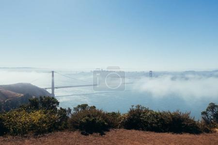 Photo for Overlook view of golden gate bridge emerging through blue hazed fog - Royalty Free Image