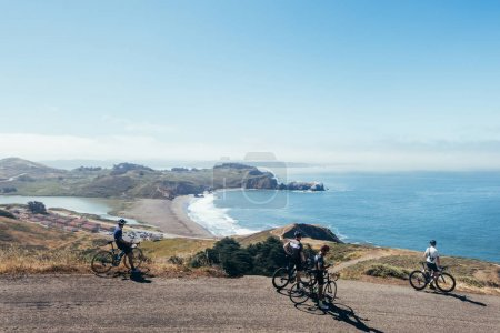 Photo for Group of cyclists descending windy narrow road next to bay with fog and water and blue sky - Royalty Free Image