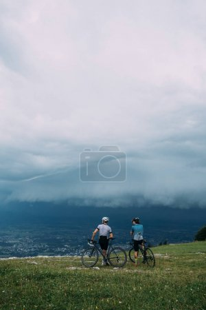 Photo for Two friends cyclists stopped near beautiful green lushious mountians - Royalty Free Image