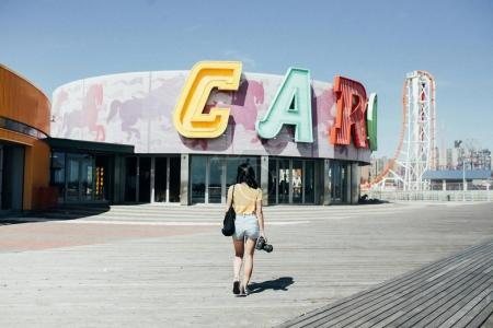 Photo pour Étudiante avec des promenades de caméra, explore la promenade abandonnée de carnaval - image libre de droit
