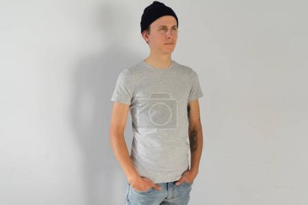 Photo pour Vue frontale à la séduisante et beau jeune homme avec des tatouages de bras hipster authentique, en bonnet bleu, en gris maquette simple t-shirt de coton organique, isolé sur fond blanc - image libre de droit