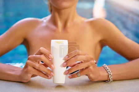 Woman holding sunscreen lotion