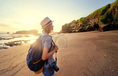 Photo for Tourism and photography. Young traveling woman with camera and rucksack walking by sea beach. - Royalty Free Image