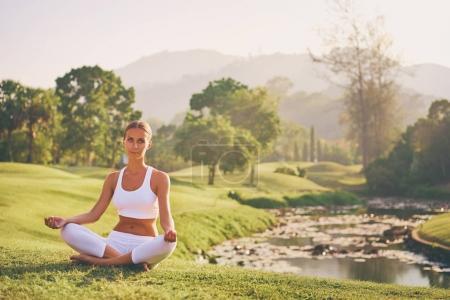 Photo pour Yoga au parc avec vue sur les montagnes, avec lumière du soleil. Jeune femme en pose de lotus assis sur l'herbe verte. Concept de calme et de méditation . - image libre de droit
