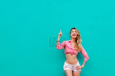 Photo for Your text here. Amazed beautiful young woman with blond long hair pointing up while standing against green wall. - Royalty Free Image