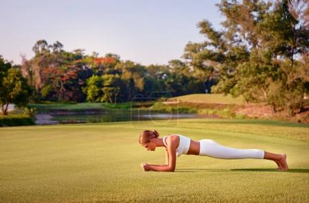 Photo for Exercising at park with view of the lake. Young woman in plank pose standing on green grass. Concept of physical activity. - Royalty Free Image