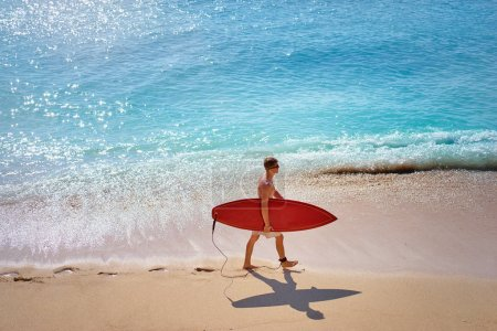 Young man carrying surf board