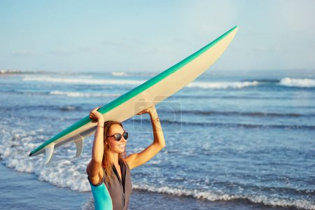 Young woman holding surf board