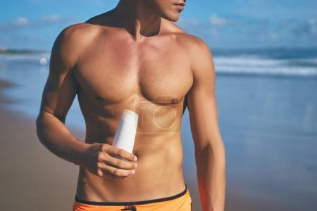 Man holding sunscreen lotion