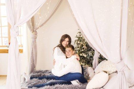 Photo pour Jeune beau couple assis au lit dans une belle pièce blanche et souriant - image libre de droit