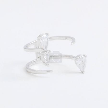 Luxurious silver jewelry ring with transparent crystals, rhinestones drops, on a grey background