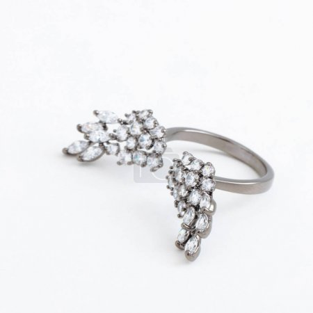 Luxurious silver jewelry ring with wings of crystals with a gray background