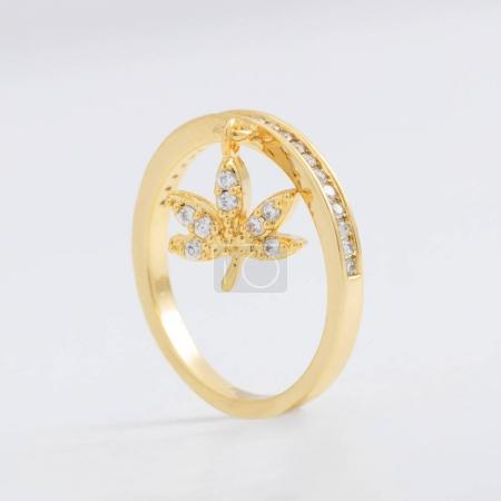 Luxurious beautiful gold jewelry ring with crystals and rhinestones, with a decorative leaf on a gray background