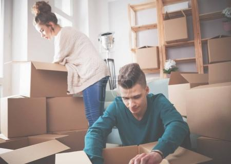 Photo for Young couple moving in new home and unpacking boxes - Royalty Free Image