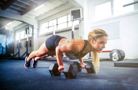 Photo for Woman working out with dumbbells doing push ups training at crossfit gym - Royalty Free Image