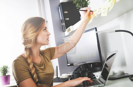 Woman working on computer at home office taking notes