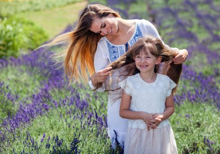 Family portrait in lavender field, mother and daughter having fun