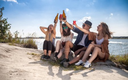 Photo for Friends having fun and drinking at the beach, freedom positive mood - Royalty Free Image