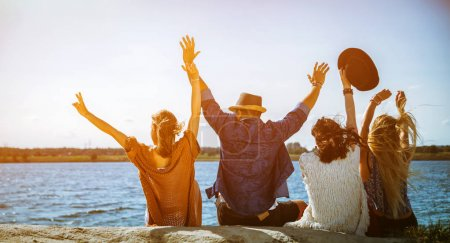 Group of friends having fun at the beach on sunny day
