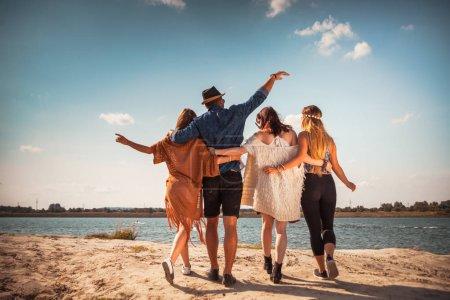 Foto de Grupo de amigos felices caminando en la playa, estado de ánimo positivo - Imagen libre de derechos