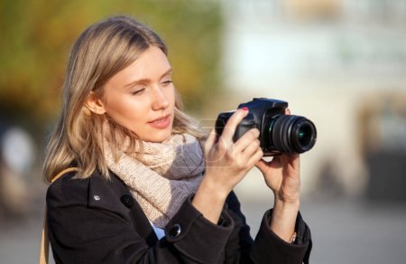 Tourist girl taking picture with camera during walk in the city