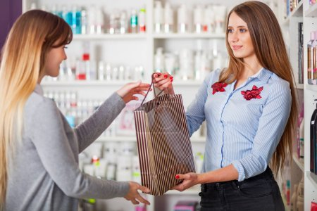 Saleswoman at beauty store giving shopping bag full of cosmetics to customer