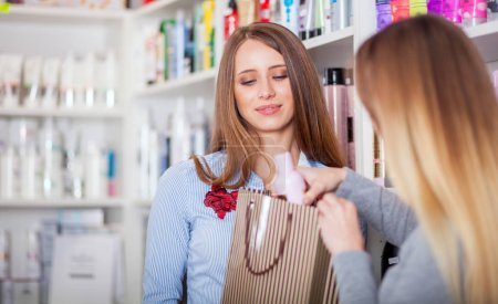 Saleswoman and customer at beauty store putting cosmetics into shopping bag