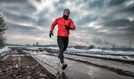 Photo for Athlete running in dirty puddle at winter time, outdoor exercise - Royalty Free Image