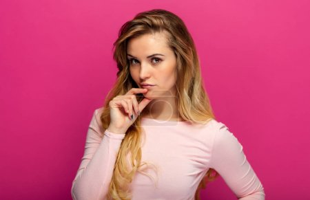Beautiful girl with on pink background thinking about something,