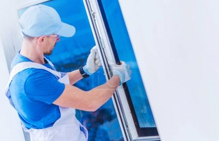 Photo for Window Replacement Installation by Professional Caucasian Construction Worker. Home Building or Remodeling Photo Concept. - Royalty Free Image