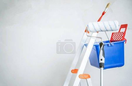Photo pour Équipement de peinture de pièce. Échelle, pinceau à peinture et rouleau . - image libre de droit