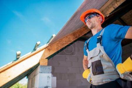 Photo pour Fiers entrepreneur de constructeur de maison caucasien se préparant pour la finition de toit. Concept de construction de maison . - image libre de droit