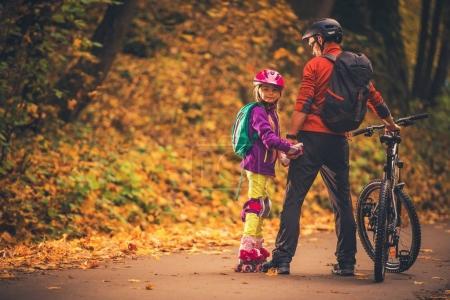Photo pour Activités de plein air familiales. Père et fille dans le parc. Patins à roulettes et vélo . - image libre de droit