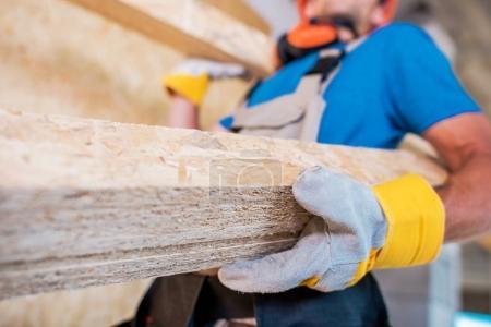 Foto de Trabajador con materiales de madera en las manos. Fotografía de cerca. Lugar de construcción . - Imagen libre de derechos