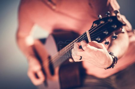 Photo for Caucasian Musician Playing Acoustic Guitar. Hand on Guitar Strings Closeup Photo. Music Performing. - Royalty Free Image