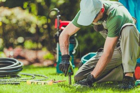 Photo pour Installation d'arroseurs de champ de gazon par installateur professionnel de systèmes de jardin caucasien . - image libre de droit